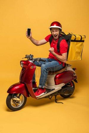 Photo pour Heureux livreur avec sac à dos sur scooter tenant smartphone et montrant geste oui sur fond jaune - image libre de droit