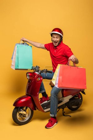 Photo for Happy delivery man in red uniform with shopping bags on scooter on yellow background - Royalty Free Image