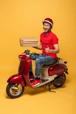 Photo for Smiling delivery man in red uniform holding pizza boxes and showing thumb up on scooter on yellow background - Royalty Free Image