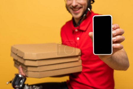 Photo for Cropped view of happy delivery man in red uniform holding pizza boxes and smartphone with blank screen isolated on yellow - Royalty Free Image