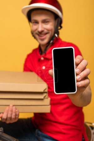 Photo for Selective focus of happy delivery man in red uniform holding pizza boxes and smartphone with blank screen isolated on yellow - Royalty Free Image