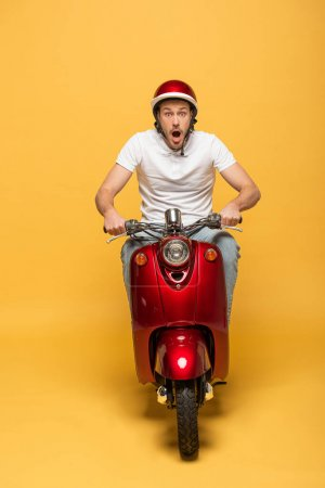 Photo for Shocked delivery man in helmet riding scooter on yellow background - Royalty Free Image