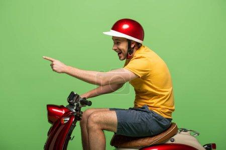 Photo pour Vue latérale de heureux livreur homme en jaune uniforme pointant avec le doigt sur scooter isolé sur vert - image libre de droit