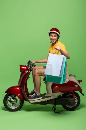 Photo for Side view of smiling delivery man in yellow uniform and helmet holding shopping bags on scooter on green - Royalty Free Image