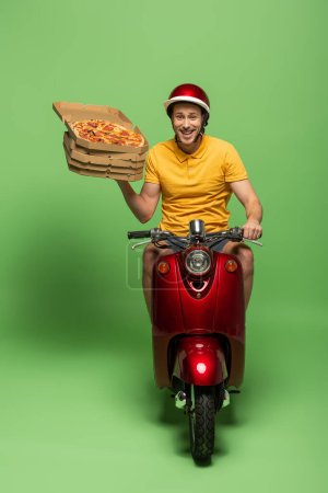 Photo for Delivery man in yellow uniform on scooter delivering pizza on green - Royalty Free Image
