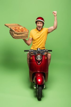 Photo for Happy delivery man in yellow uniform on scooter delivering pizza and showing yes gesture on green - Royalty Free Image