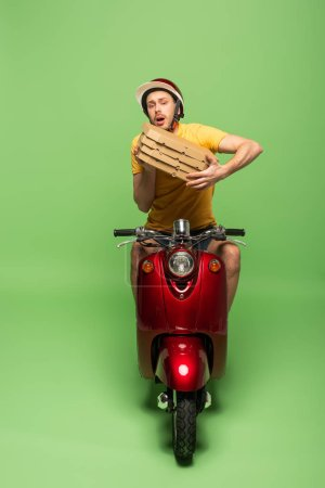 Photo for Worried delivery man in yellow uniform on scooter with pizza boxes on green - Royalty Free Image