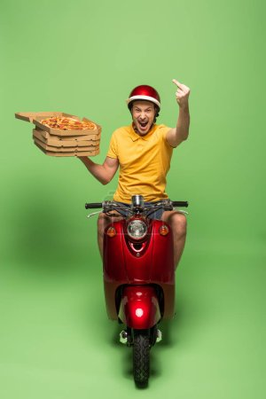 Photo for Excited delivery man in yellow uniform with open mouth on scooter delivering pizza and showing middle finger on green - Royalty Free Image