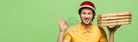 Photo for Smiling delivery man in yellow uniform delivering pizza and showing ok sign isolated on green, panoramic shot - Royalty Free Image