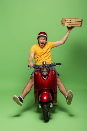 Photo for Mad delivery man in yellow uniform on scooter delivering pizza on green - Royalty Free Image