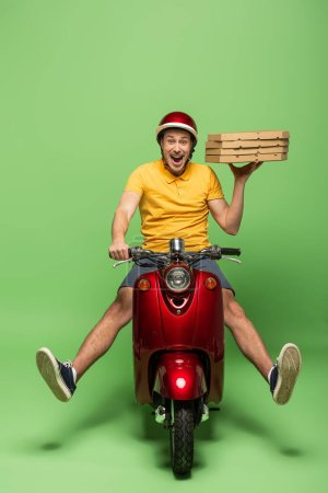 Photo for Crazy delivery man in yellow uniform on scooter delivering pizza on green - Royalty Free Image