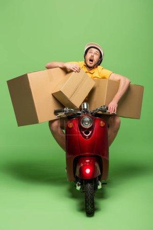 Photo pour Livreur en uniforme jaune avec bouche ouverte sur scooter avec boîtes sur vert - image libre de droit