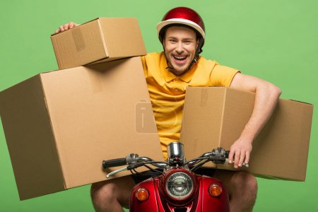 Photo for Happy delivery man in yellow uniform on scooter with boxes isolated on green - Royalty Free Image