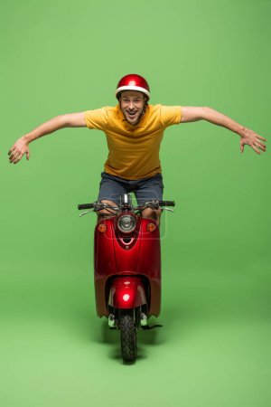 Photo for Happy delivery man in yellow uniform and helmet doing trick on scooter on green - Royalty Free Image