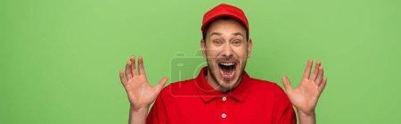 Photo pour Excité livreur en uniforme rouge montrant les mains isolées sur vert, panoramique coup - image libre de droit