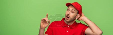 Foto de Excitado repartidor en uniforme rojo mostrando gesto idea aislado en verde, tiro panorámico - Imagen libre de derechos