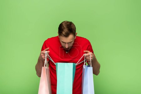 Photo for Man looking in shopping bags isolated on green - Royalty Free Image