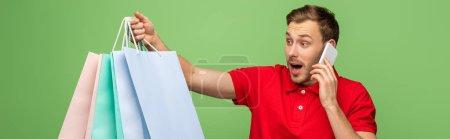 Photo pour Homme choqué tenant des sacs à provisions tout en parlant sur smartphone isolé sur vert, plan panoramique - image libre de droit