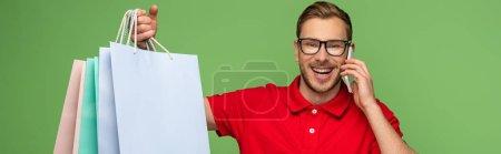 Photo pour Homme heureux dans des lunettes tenant des sacs à provisions et parlant sur un téléphone intelligent isolé sur une photo panoramique verte - image libre de droit