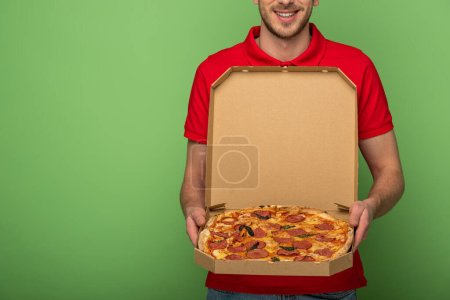 Photo for Cropped view of smiling delivery man in red uniform holding pizza box on green - Royalty Free Image