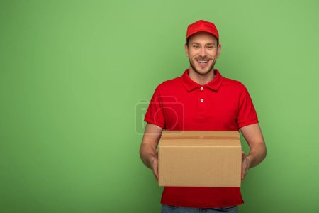 Photo for Smiling delivery man in red uniform holding parcel on green - Royalty Free Image