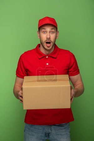 Photo for Shocked delivery man in red uniform holding parcel on green - Royalty Free Image