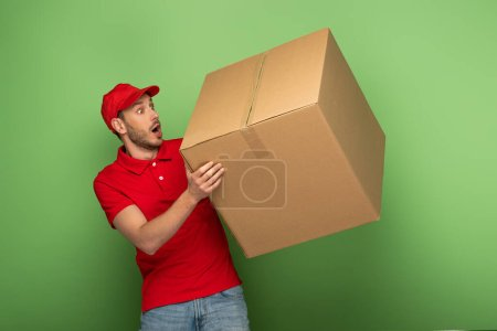 Photo for Shocked delivery man in red uniform holding huge parcel on green - Royalty Free Image