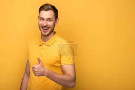 Photo pour Heureux bel homme en tenue jaune montrant pouce vers le haut sur fond jaune - image libre de droit