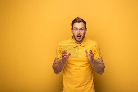 impactado hombre guapo en traje amarillo gesto sobre fondo amarillo