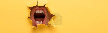 Photo pour Vue recadrée de la bouche ouverte dans un trou de papier jaune - image libre de droit