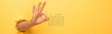 Photo pour Vue recadrée de l'homme montrant ok signe à travers le trou de papier jaune, vue panoramique - image libre de droit