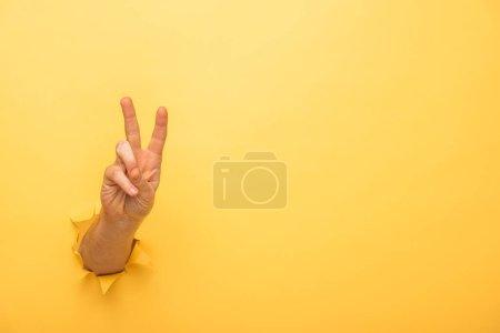 Photo pour Vue recadrée de l'homme montrant signe de paix à travers un trou de papier jaune - image libre de droit
