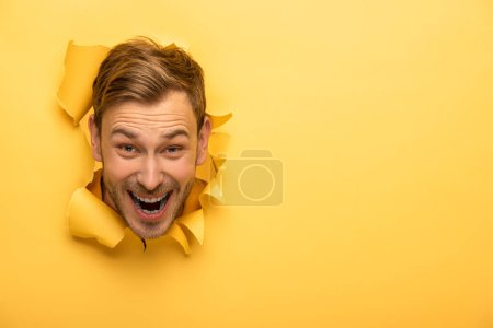 Photo pour Fou bel homme avec la tête dans le trou de papier jaune - image libre de droit