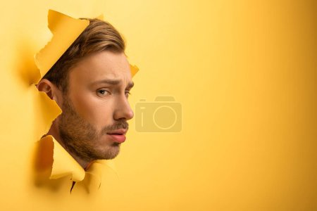 sad handsome man with head in yellow paper hole