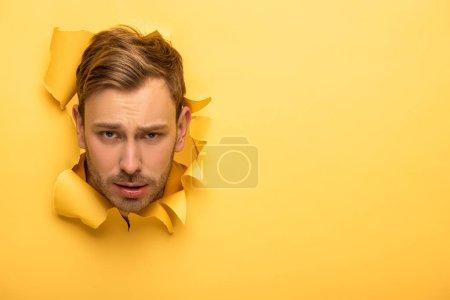 Photo pour Triste homme beau avec la tête dans le trou de papier jaune - image libre de droit