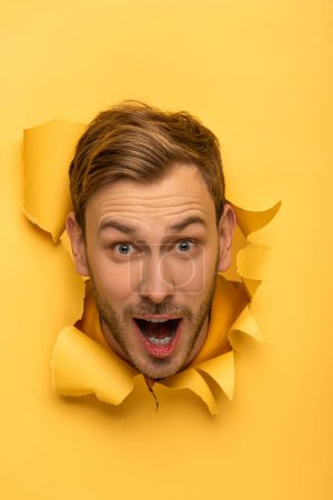 Photo for Excited handsome man with head in yellow paper hole - Royalty Free Image