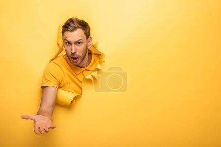 Photo pour Confus bel homme en tenue jaune dans un trou de papier jaune - image libre de droit