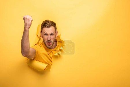 Photo pour En colère bel homme en tenue jaune dans le trou de papier jaune montrant poing - image libre de droit