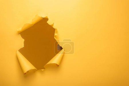 Photo pour Trou déchiré dans la texture du papier jaune avec espace de copie - image libre de droit