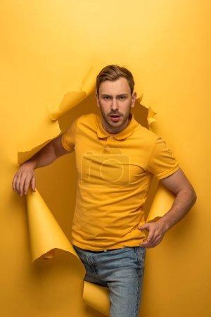 Photo pour Bel homme en tenue jaune marchant à travers un trou de papier jaune - image libre de droit
