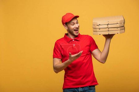 Photo for Happy delivery man in red uniform pointing with hand at pizza boxes isolated on yellow - Royalty Free Image