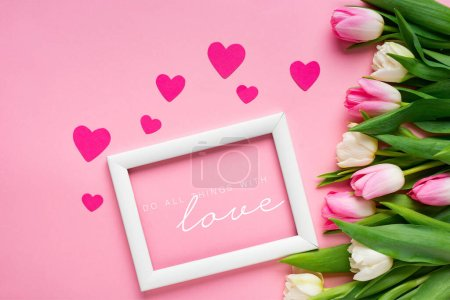 Photo for Top view of white frame with do all thing with love illustration near tulips and hearts on pink background - Royalty Free Image
