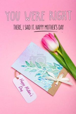 Photo pour Vue du dessus de la carte de vœux avec joyeux lettrage de la fête des mères sur étiquette en papier et tulipe sur fond rose - image libre de droit