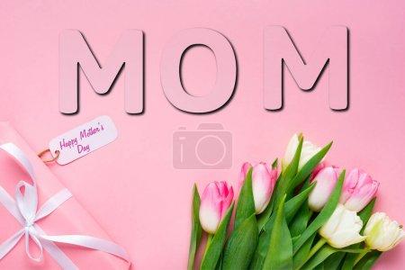 Photo pour Vue du dessus du cadeau avec joyeux lettrage de la fête des mères sur l'étiquette en papier près des tulipes sur fond rose, illustration maman - image libre de droit