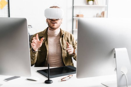 Photo for Excited 3d artist in virtual reality headset gesturing near computers and graphics tablet on table - Royalty Free Image