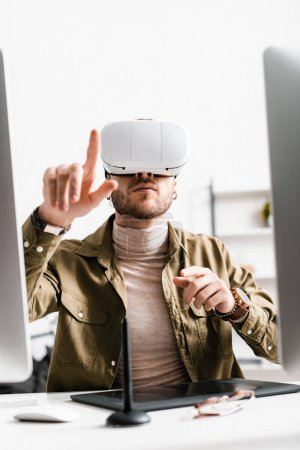 Photo for Selective focus of digital designer in virtual reality headset pointing with finger near graphics tablet and computers on table - Royalty Free Image