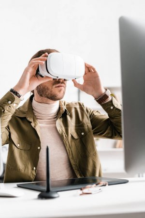 Photo for Selective focus of 3d artist using virtual reality headset near graphics tablet and computer on table in office - Royalty Free Image