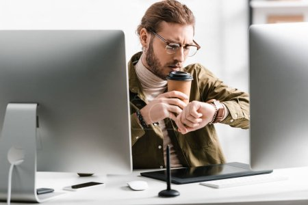 Photo for Selective focus of 3d artist looking at wristwatch while drinking coffee near digital devices on table - Royalty Free Image