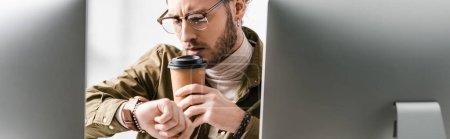 Photo pour Focus sélectif de l'artiste 3d regardant montre-bracelet tout en buvant du café près des écrans d'ordinateur sur fond blanc, prise de vue panoramique - image libre de droit