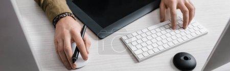Foto de Vista cruzada del diseñador digital usando teclado de computadora y ratón cerca de la tabla gráfica en la mesa, disparo panorámico. - Imagen libre de derechos